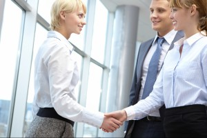 Two business women shake hands while male counterpart looks on